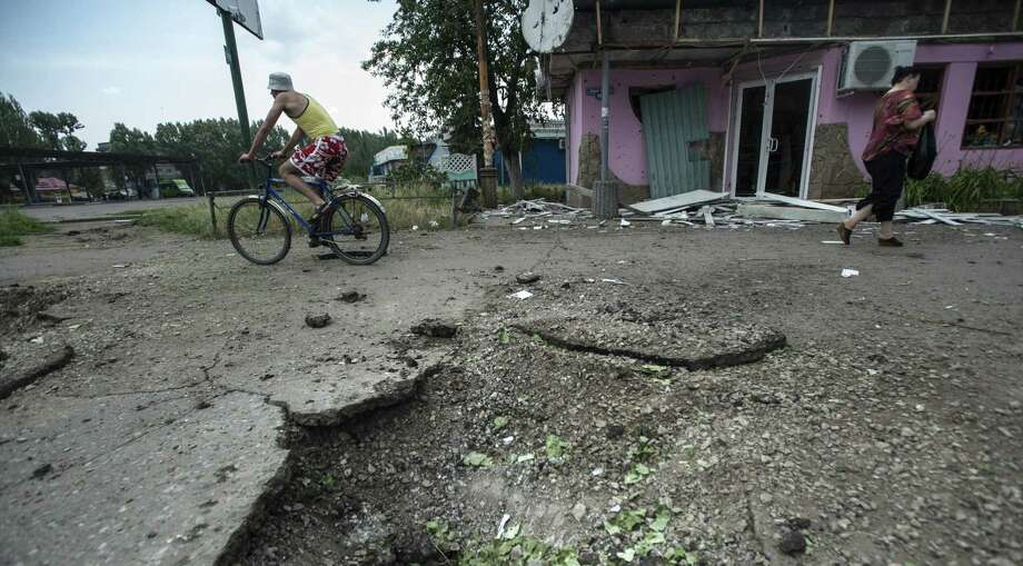 People pass a crater left by a mortar attack in Slovyansk, Ukraine. Several buildings were damaged by shelling in the eastern city, which is controlled by pro-Russian separatists. Photo: Evgeniy Maloletka, Associated Press / AP