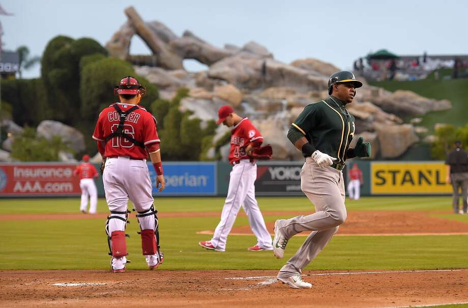 Oakland Athletics' Yoenis Cespedes, right, scores on a single by Stephen Vogt as Los Angeles Angels catcher Hank Conger, left, and starting pitcher Garrett Richards look on during the second inning of a baseball game against the Los Angeles Angels, Monday, June 9, 2014, in Anaheim, Calif. (AP Photo/Mark J. Terrill) Photo: Mark J. Terrill, Associated Press