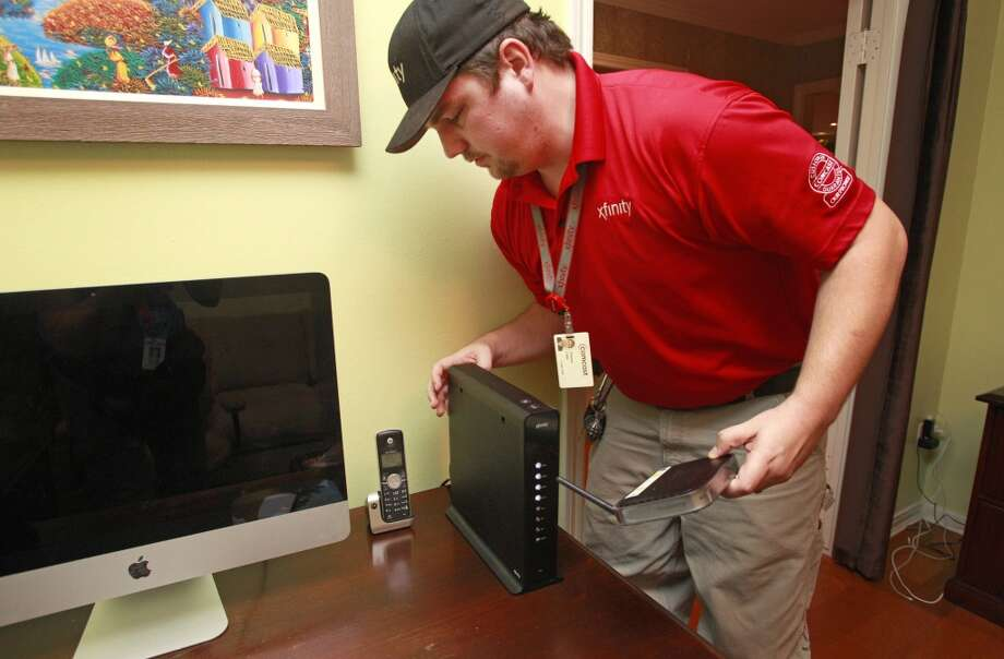 Thomas Cable, a Comcast installation technician, installs an XB-3 wireless gateway in a home Monday, June 9, 2014, in Houston. Photo: Melissa Phillip, Houston Chronicle