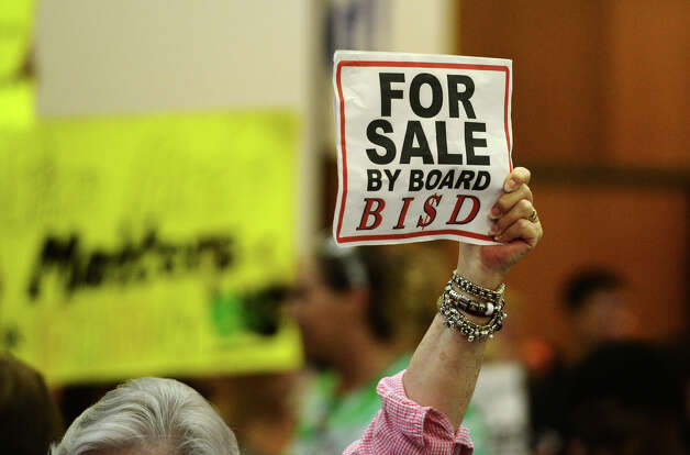 Demonstrators hold up signs before the beginning of Monday night's school board meeting. The BISD board of trustees met Monday night to discuss reduction in force measures, which may possibly lead to the elimination of more than 200 positions. Photo taken Monday 6/9/14 Jake Daniels/@JakeD_in_SETX Photo: Jake Daniels / ©2014 The Beaumont Enterprise/Jake Daniels