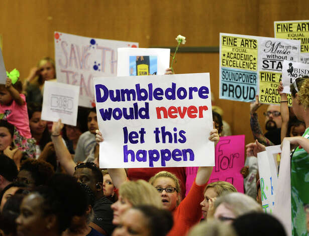 Demonstrators hold up signs before the beginning of Monday night's school board meeting. The