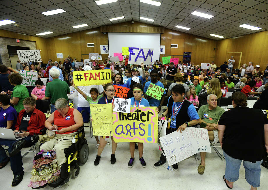 Demonstrators hold up signs before the beginning of Monday night's school board meeting. The BISD board of trustees met Monday night to discuss reduction in force measures, which may possibly lead to the elimination of more than 200 positions.