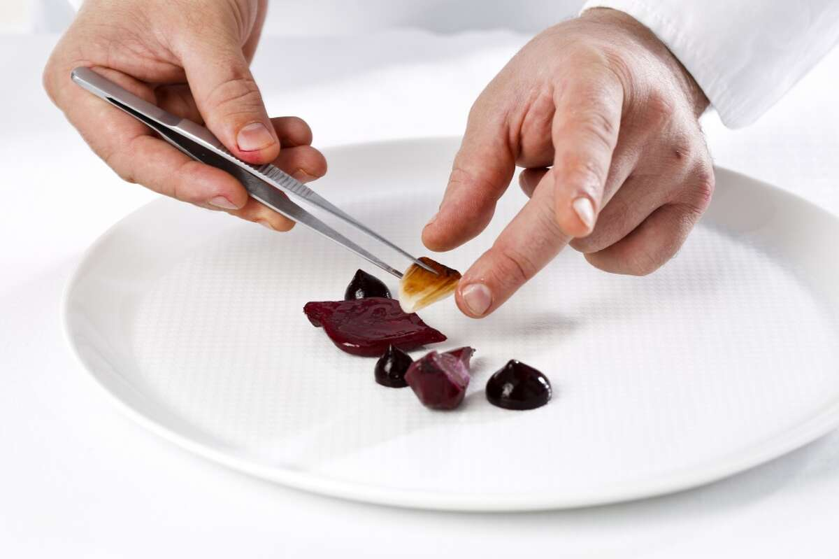 Chef David Breeden, chef de cuisine at The French Laundry, plates a dish called,