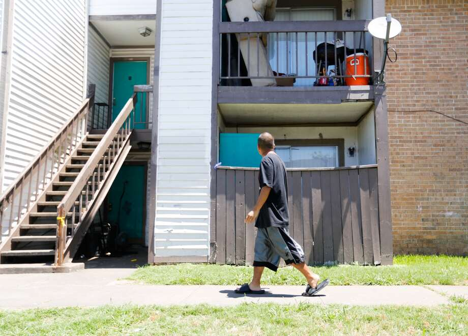 Alex Mendoza, 19, walks past the Happy Home Apartment complex residence where A girl, believed to be about 9 years old, was found dead and wrapped in blankets Monday evening. Photo: Johnny Hanson, Houston Chronicle
