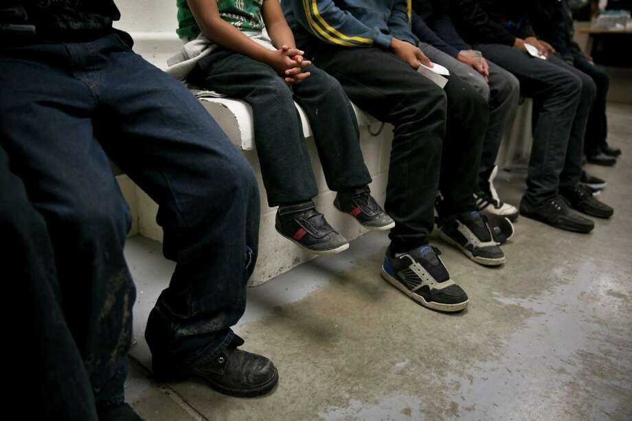 A child from Honduras sits with older youths being processed at a U.S. Border Patrol station in Brownsville. The surge in unaccompanied children crossing the South Texas border illegally has created a humanitarian crisis. The Obama administration has taken steps to help, but more must be done. Photo: Todd Heisler, New York Times / NYTNS