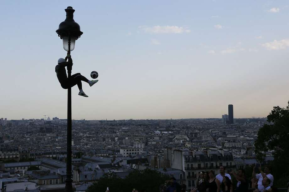 Just for kicks: Iya Traore, a former professional soccer player, can dribble a soccer ball while hanging on a lamppost  