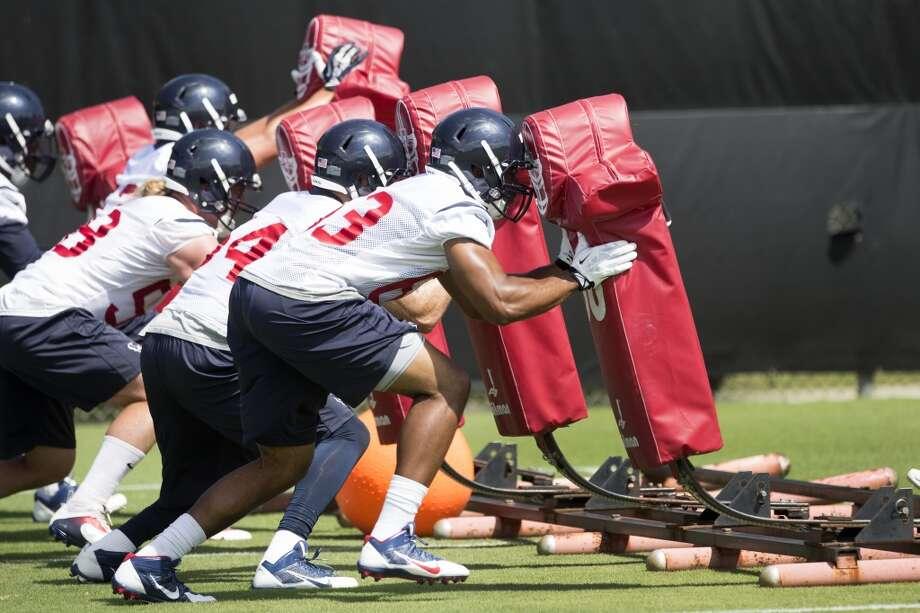 Texans linebacker Terrance Lloyd (63) hits a blocking sled. Photo: Brett Coomer, Houston Chronicle