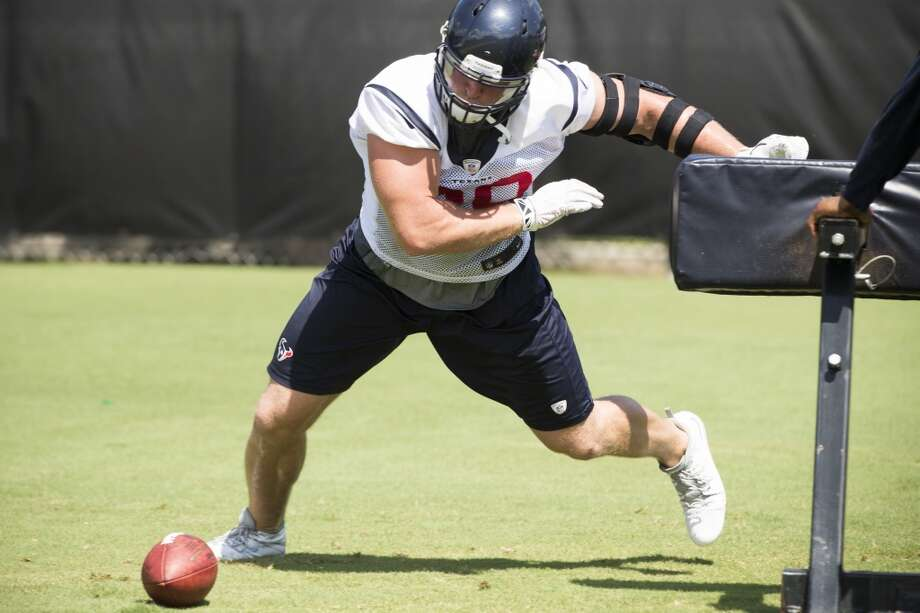Day 8 - June 10  Defensive end J.J. Watt goes after a football on the ground after hitting a blocking sled. Photo: Brett Coomer, Houston Chronicle