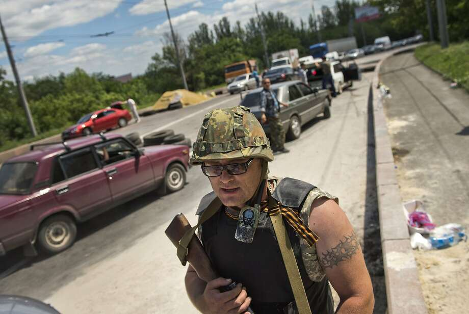 """A pro-Russian militia member from the """"Russian Orthodox Army"""" stands at a checkpoint near the airport of the eastern city of Donetsk. Photo: Daniel Mihailescu, AFP/Getty Images"""
