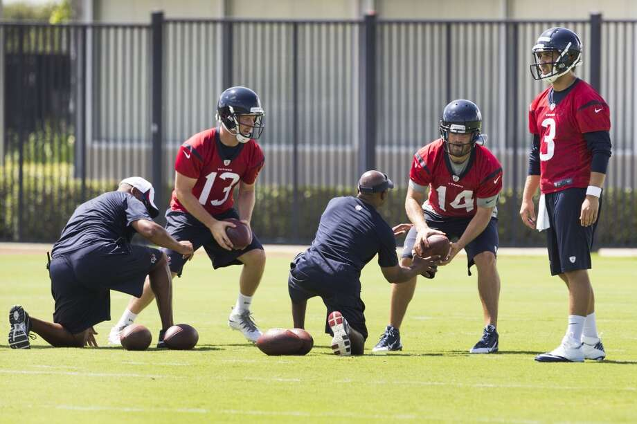 Texans quarterbacks T.J. Yates (13) and Ryan Fitzpatrick (14) take snaps with Tom Savage (3) looking on. Photo: Brett Coomer, Houston Chronicle