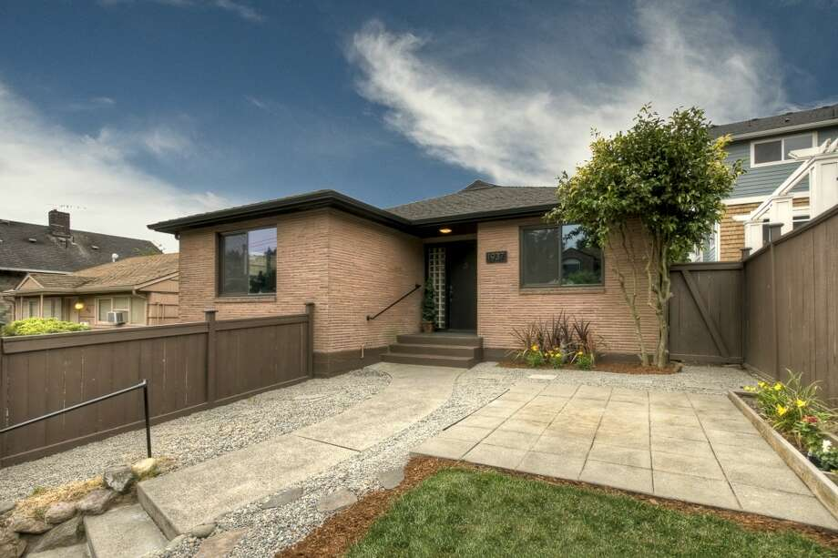 We'll start with the newest home, 1937 10th Ave. W., which was built in 1953. It's 2,600 square feet, with two bedrooms, a bathroom, a living room, a fireplace and a kitchen on each of its two levels, plus an upper-level deck, front and rear patios and views of Elliott Bay on a 4,800-square-foot lot. It's listed for $789,000. Photo: Vicaso, Courtesy Ione McCarthy/RSVP Real Estate