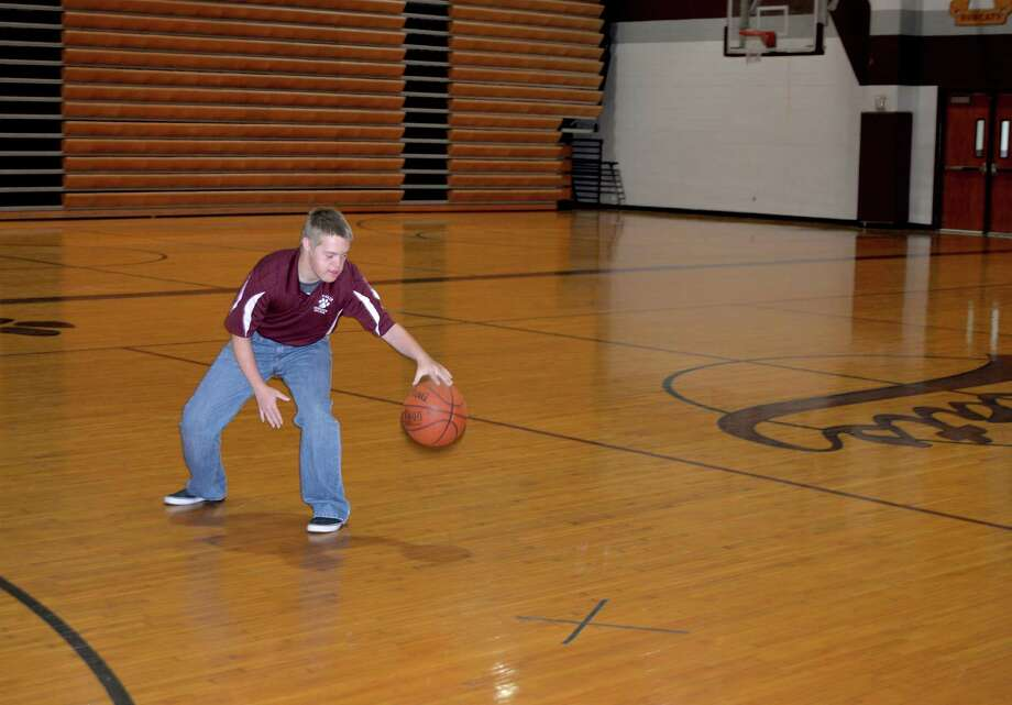 "Cy-Fair High School senior Carson Berg, 18, practices basketball, his favorite sport. One of a set of triplets, Berg, who has Down syndrome, has a positive attitude, is a good athlete and is ""extremely social,"" according to principal Michael Smith. Photo: Lindsay Peyton"