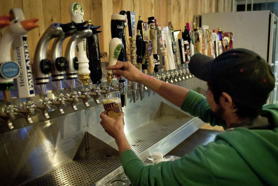 Bartender Tony Lopez draws a beer at The Friendly Spot in San Antonio. The bar brings new meaning to the word inviting, with beer safe to serve to man's best friend. Photo: Express-News File Photo / San Antonio Express-News