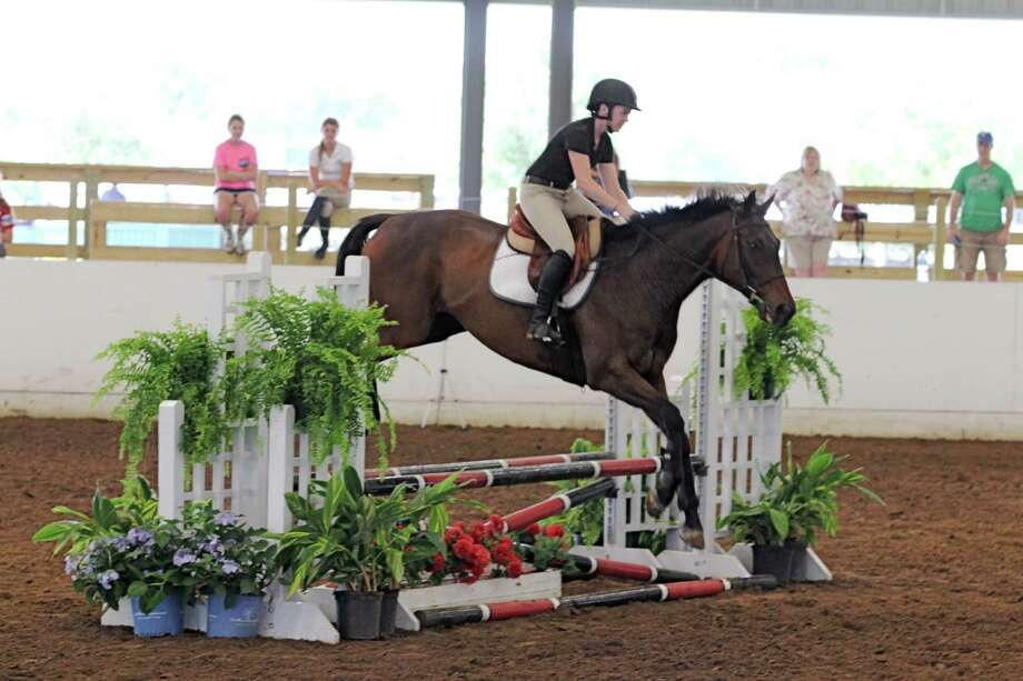 Emily Albitz, 19, of Katy rides Whiskey & Grits in the Ittey Bittey Jumpers competition in May at the Great Southwest Equestrian Center in Katy.Emily Albitz, 19, of Katy rides Whiskey & Grits in the Ittey Bittey Jumpers competition in May at the Great Southwest Equestrian Center in Katy. Photo: Suzanne Rehak, Freelance Photographer