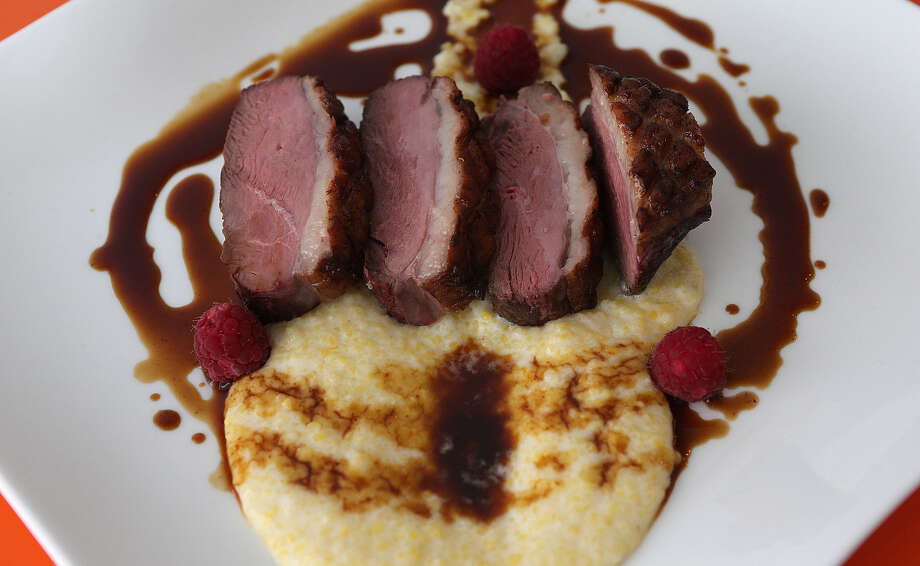 The Hudson Valley duck breast comes with polenta and raspberry sauce at Saveur 209, which offers authentic French food. The restaurant's décor complements the bright colors and tones of Saveur's dishes. Photo: Express-News File Photo / © 2013 San Antonio Express-News