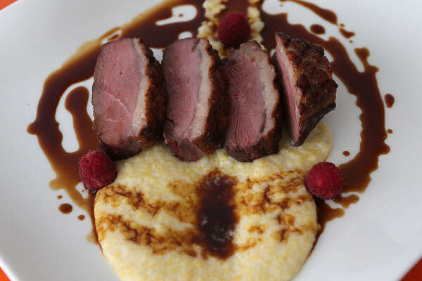 The Hudson Valley duck breast comes with polenta and raspberry sauce at Saveur 209, which offers authentic French food. The restaurant's décor complements the bright colors and tones of Saveur's dishes.