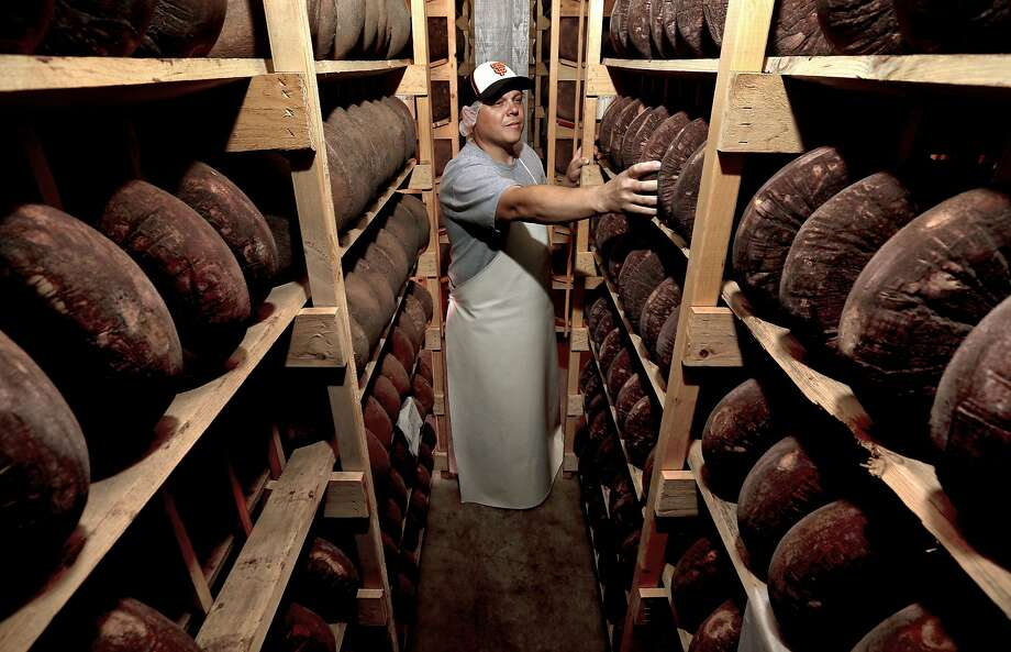 Cheesemaker Gabe Luddy with rounds Dry Monterey Jack cheese being aged on wooden racks at the Vella Cheese Co. in Sonoma, Calif. as seen on Tuesday June 10, 2014. Photo: Michael Macor, The Chronicle