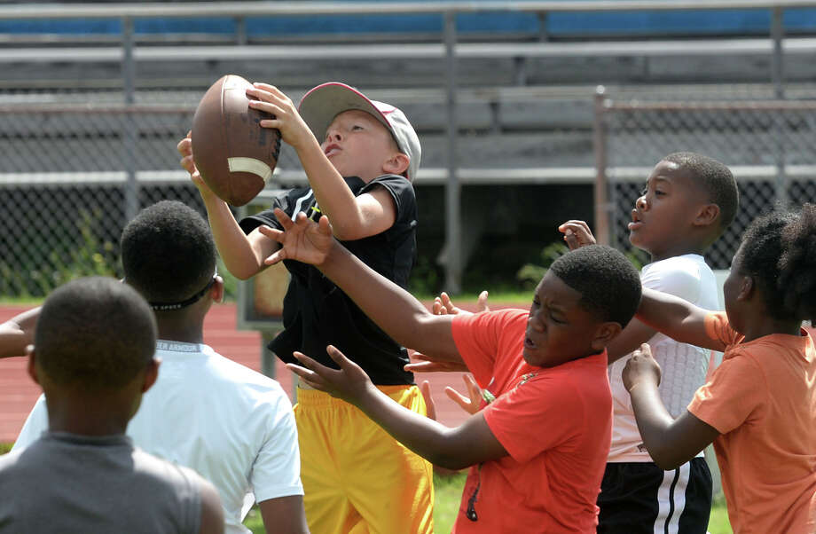 Bryce West, 10, makes one of several catches during West Brook's football camp on Monday. Photo taken Monday, June 09, 2014 Guiseppe Barranco/@spotnewsshooter Photo: Guiseppe Barranco, Photo Editor