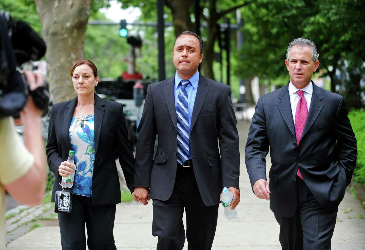 Elson Morales, center, walks with his wife and his attorney, Michael Fitzpatrick, to the U.S. District Court in Bridgeport, Conn. on Tuesday, June 10, 2014, where he pleaded guilty to stomping a Tasered man in Beardsley Park. Morales, a 12-year veteran of the Bridgeport Police Department, faces up to a year in prison for the misdemeanor charge of violating a personâÄôs civil rights.