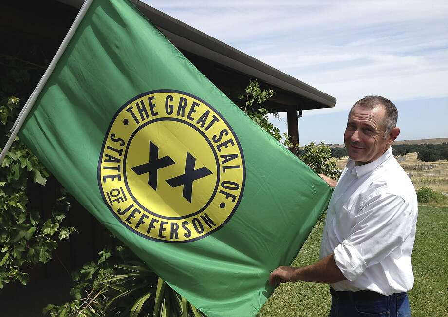 Tom Knorr holds a flag for the proposed state of Jefferson in Tehama County. Photo: Terry Chea, Associated Press