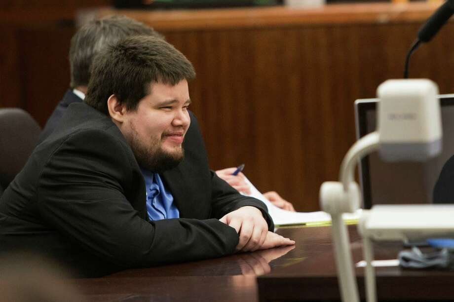 Justin Wayne Parris,27, sits at the defense table with his attorney, Jerome Godinich, listening to testimony during his murder trial at the Harris County Courthouse Tuesday, June 10, 2014, in Houston. Prosecutors Tuesday said Parris is on trial for the murder of his 81-year-old grandfather, in which he allegedly  decapitated him with hedge clippers. Police found Justin Wayne Parris with blood smears on his pants and shirt at the elder man's home in the 900 block of Lamonte on November 6, 2009, according to court records. Photo: Brett Coomer, Houston Chronicle / © 2014 Houston Chronicle