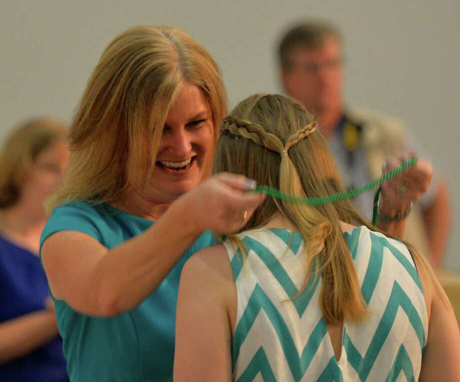 Diane Irwin, K-12 science coordinator for the Ballston Spa Central School District, left, puts the cord of graduation over the head of one of the students Tuesday morning, June 10, 2014, during a graduation ceremony for the Clean Technologies & Sustainable Industries Early College High School in Malta, N.Y.  (Skip Dickstein / Times Union) Photo: SKIP DICKSTEIN / 00027283A
