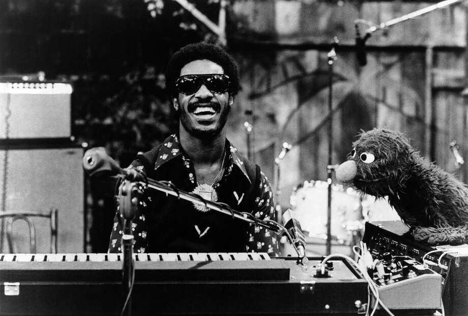 """The list of Stevie Wonder chart-topping hits is so mind-bogglingly long that we'll mention just a few here and hope you know the rest. It's impossible to say which is his best, but with a list of mega-hits such as, """"Sir Duke"""" (1976), """"Superstition"""" (1972), """"Signed, Sealed, Delivered (1970), """"I Wish"""" (1976), """"Higher Ground (1973), and """"My Cherie Amour"""" (1969), Wonder's Motown dominance goes without saying. Here, Stevie Wonder appears on Sesame Street with Sesame Street character Grover to perform """"Superstition"""" in 1973. Photo: Echoes, Getty / Redferns"""