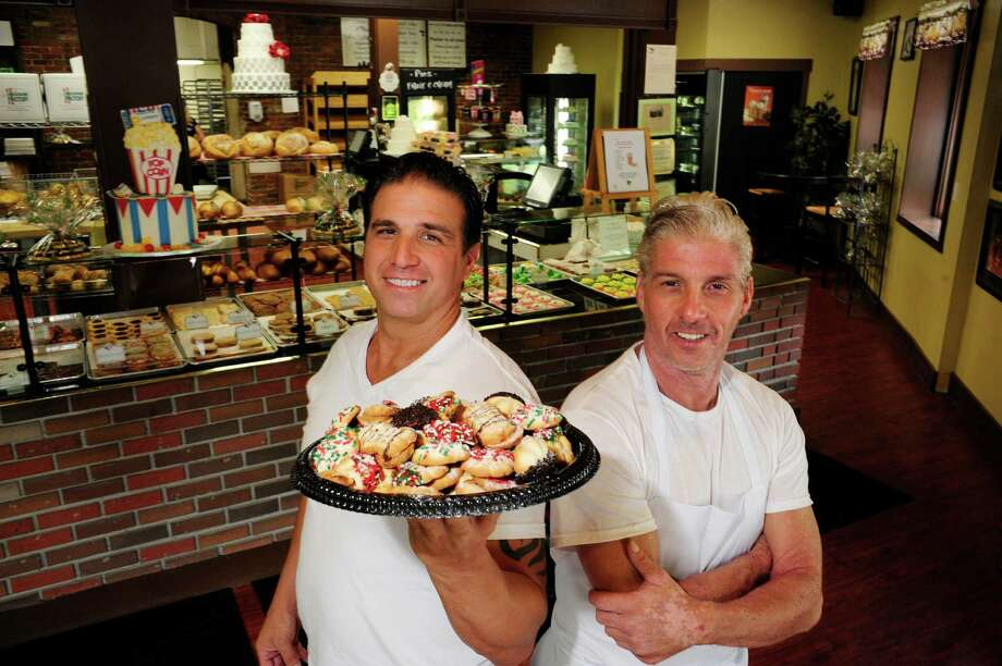 Brothers and co-owners of The Cookie Factory, Chris Alberino, left, and Joe Alberino pose with a plate of their Italian butter cookies at their store on Tuesday, June 10, 2014, in Troy, N.Y.  (Paul Buckowski / Times Union) Photo: Paul Buckowski / 00027281A