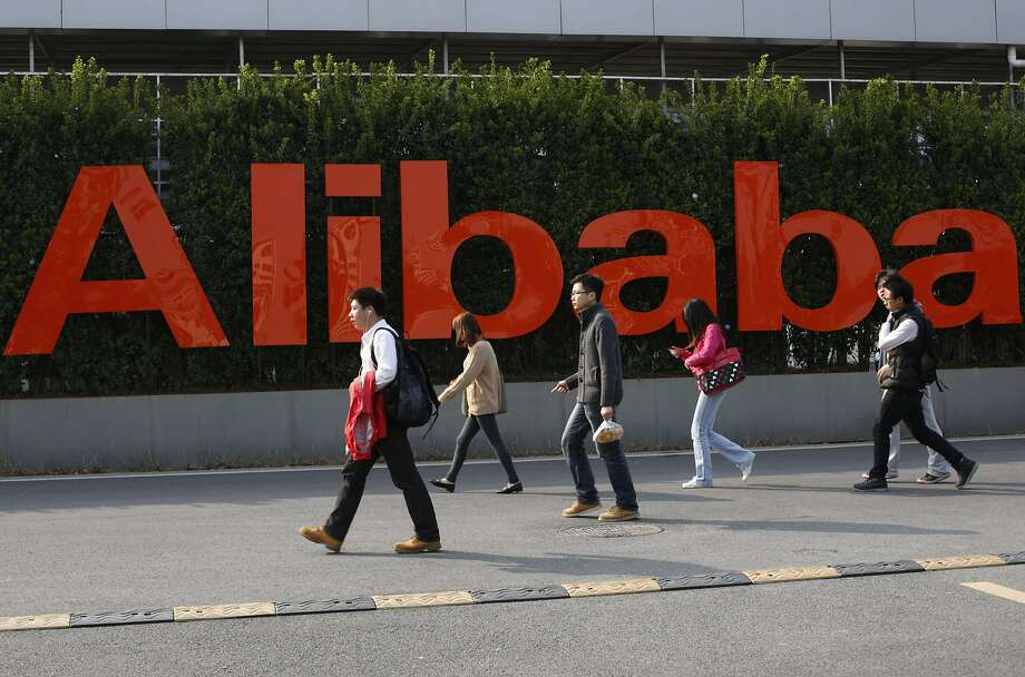 FILE - In this March 17, 2014 file photo, people walk past a company logo at the headquarters of Alibaba Group in Hangzhou, in eastern China's Zhejiang province. The Monster Tron T1 headphones sold on Chinese e-commerce giant Alibaba's Taobao site are a tempting offer for audiophiles looking for a good price on authentic state-of-the-art hi-fi equipment but the California company, best known for its audio-visual cables, said Monday, May 27, 2014 that 99.5 percent of purported Monster products sold on Alibaba sites are fakes, based on thousands of listings the company's investigators have examined over the years. (AP Photo)  CHINA OUT Photo: Associated Press