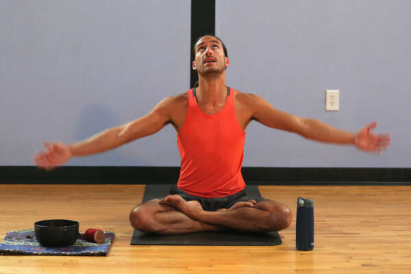 Yoga instructor Mark Bennett conducts a lunchtime class at The Synergy Studio. The studio holds more than 50 classes a week at their site in The Pearl.