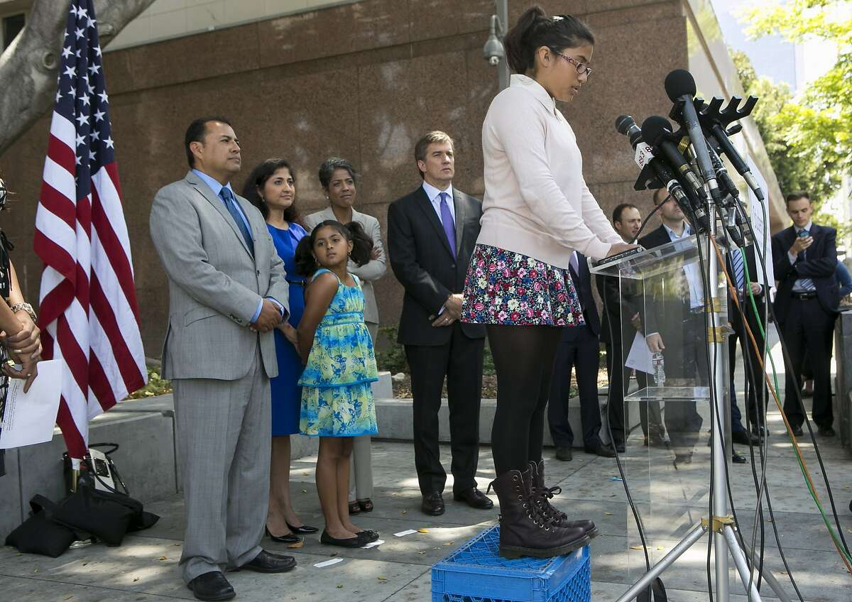 Student Julia Macias, right at lectern, a plaintiff and Los Angeles Unified School District Middle School, comments on the Vergara v. California lawsuit verdict in Los Angeles, Tuesday, June 10, 2014. Others from left, parents, Joe Macias, with wife, Evelyn, and their daughter Lucy, Russlyn Ali, Former Assistant Secretary of U.S. Education Department Office for Civil Rights, and Students Matter Board member, with Founder David Welch.