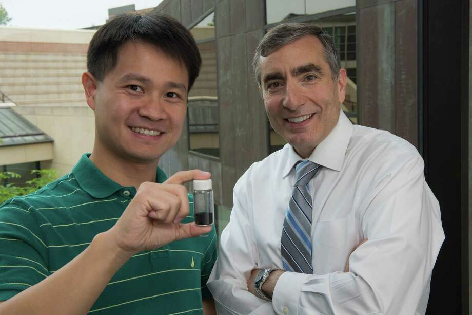 Graduate student Chih-Chau Hwang, left, and Rice University chemistry professor James Tour display a vial of powder that can capture carbon dioxide. Photo: Jeff Fitlow