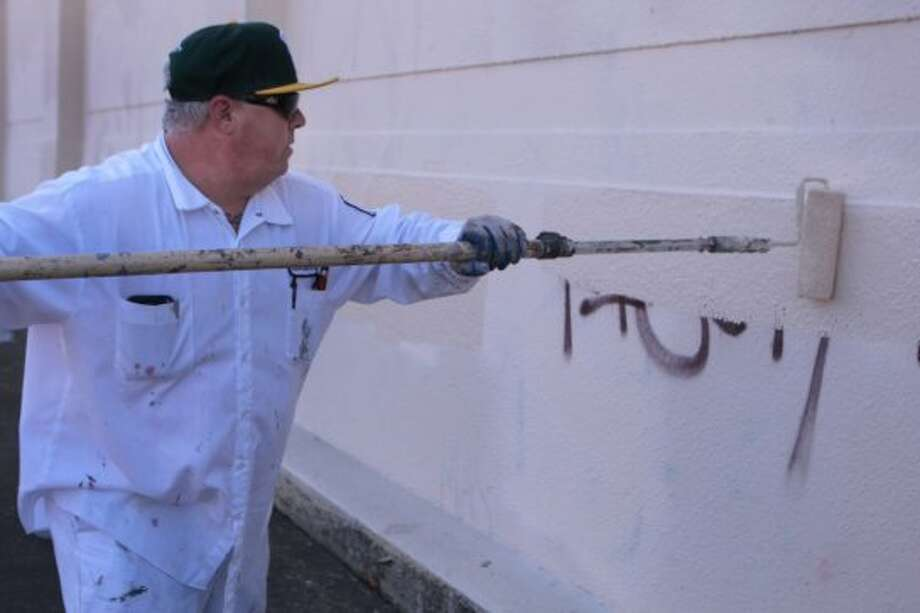 Randall Matthews with the Oakland Public Works Department paints over graffiti on an East Oakland building to help out friend Ken Houston as he cleans up and announces his run for mayor of Oakland on Tuesday, June 10, 2014 in Oakland, Calif. Photo: Kevin N. Hume, The Chronicle