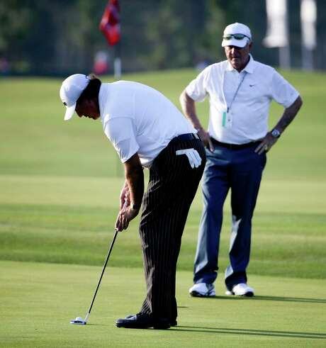 Phil Mickelson, left, tries out the claw grip as putting guru Dave Stockton keeps watch Tuesday. Photo: David Goldman, STF / AP