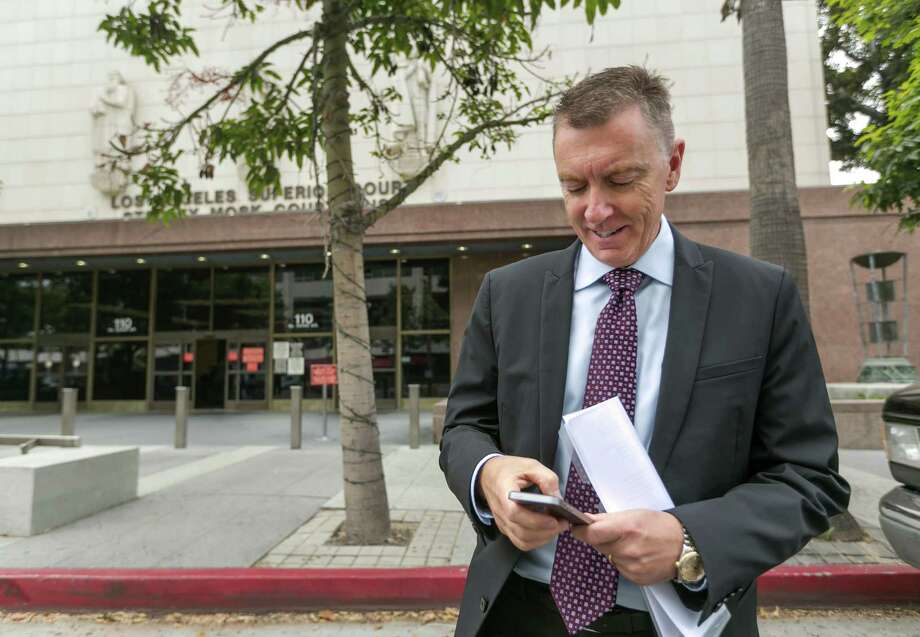 Los Angeles Unified School District Superintendent John Deasy checks his phone, while awaiting the verdict in the Vergara v. California lawsuit. Photo: Damian Dovarganes, STF / AP