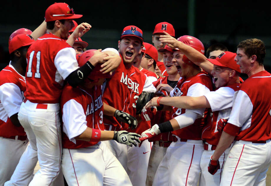 Teammates surround Edward Cleland after scoring, during Class L Baseball Semi-final action against Jonathan Law in Middletown, Conn. on Tuesday June 10, 2014. Photo: Christian Abraham / Connecticut Post