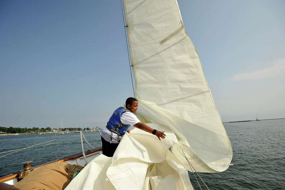 Gregory Perard helps bring in a sail during a sailboat ride on the Ticonderoga on the Long Island Sound as part of the graduation festivities associated with the Young Mariners' 10th annual graduation ceremony which was held at the Stamford Yacht Club in Stamford, Conn., on Tuesday, June 10, 2014. The Young Mariners Afterschool Enrichment Program is a STEM-based program that helps underserved and at-risk students through the universal principles of sailing. Photo: Jason Rearick / Stamford Advocate