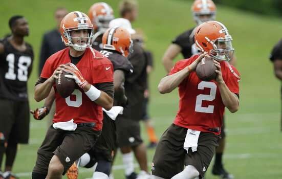 Browns starting QB Brian Hoyer (left) and backup Johnny Manziel go through drills during Tuesday's minicamp. Manziel is back at practice after partying in Texas, which didn't bother coach Mike Pettine. Photo: Mark Duncan / Associated Press / AP