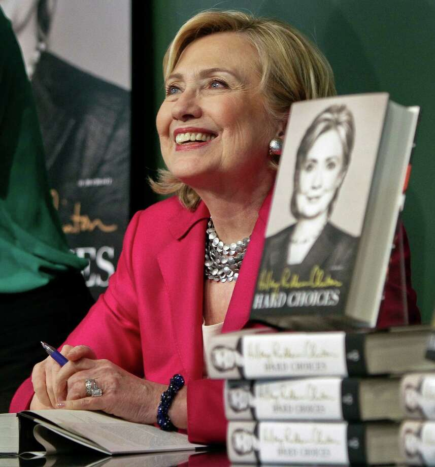 """HiIlary Rodham Clinton listens before signing a copy of her book, """"Hard Choices"""" on Tuesday June 10, 2014, at Barnes and Noble bookstore in New York.  Clinton said Tuesday that she and former President Bill Clinton """"fully appreciate how hard life is for so many Americans,"""" seeking to refine remarks she made about the pair being broke when they left the White House while on a high-profile media tour for a new book.  (AP Photo/Bebeto Matthews) Photo: Bebeto Matthews, STF / AP"""
