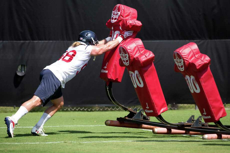Brooks Reed, taking on a tackling dummy, will start out at inside linebacker but could return to the outside. Photo: Brett Coomer, Staff / © 2014 Houston Chronicle
