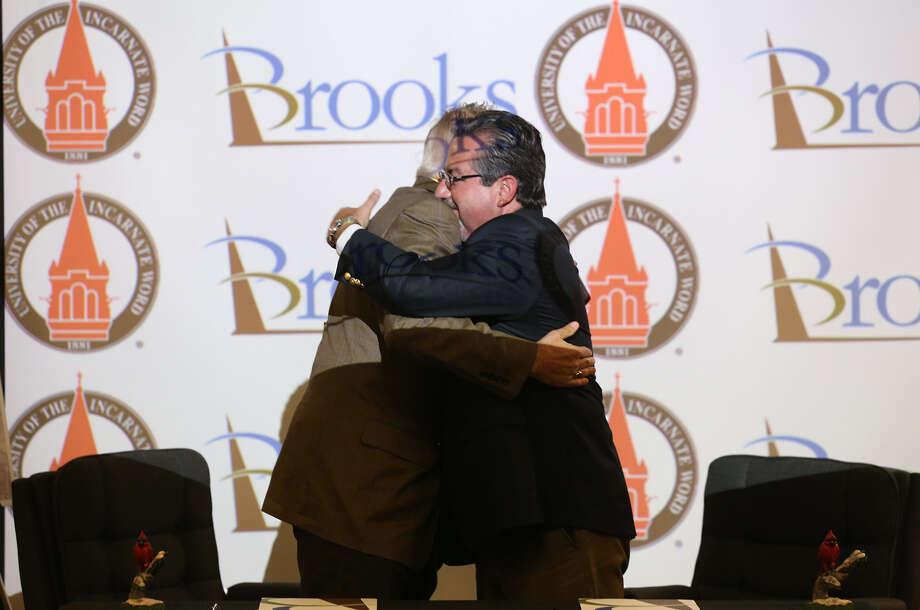 UIW President Lou Agnese (left) and Brooks City Base President and CEO Leo Gomez share an embrace. Photo: Jerry Lara / San Antonio Express-News / © 2014 San Antonio Express-News