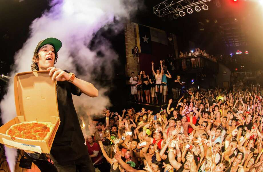 DJ Crizzly prepares to throw his signature pizza into a screaming crowd during a performance in San Marcos. Photo: Photos By Brad Candia / For The San Antonio Express-News / Photos by Brad Candia