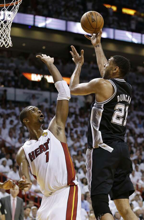 Spurs forward Tim Duncan drives to the basket over Miami Heat center Chris Bosh. Duncan scored 14 points in the win. Photo: Wilfredo Lee, Associated Press