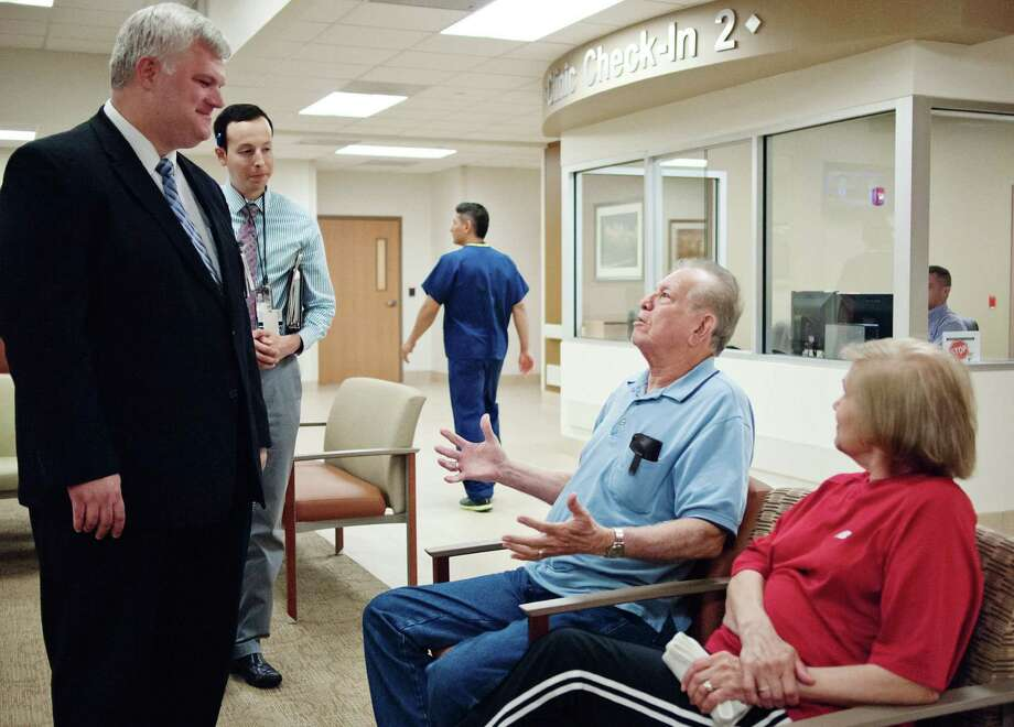 In this 2012 photo, Korean War vet Mike Nino (center) talks with an official at a VA facility in Harlingen. Photo: Jesse Mendoza / Associated Press / Valley Morning Star