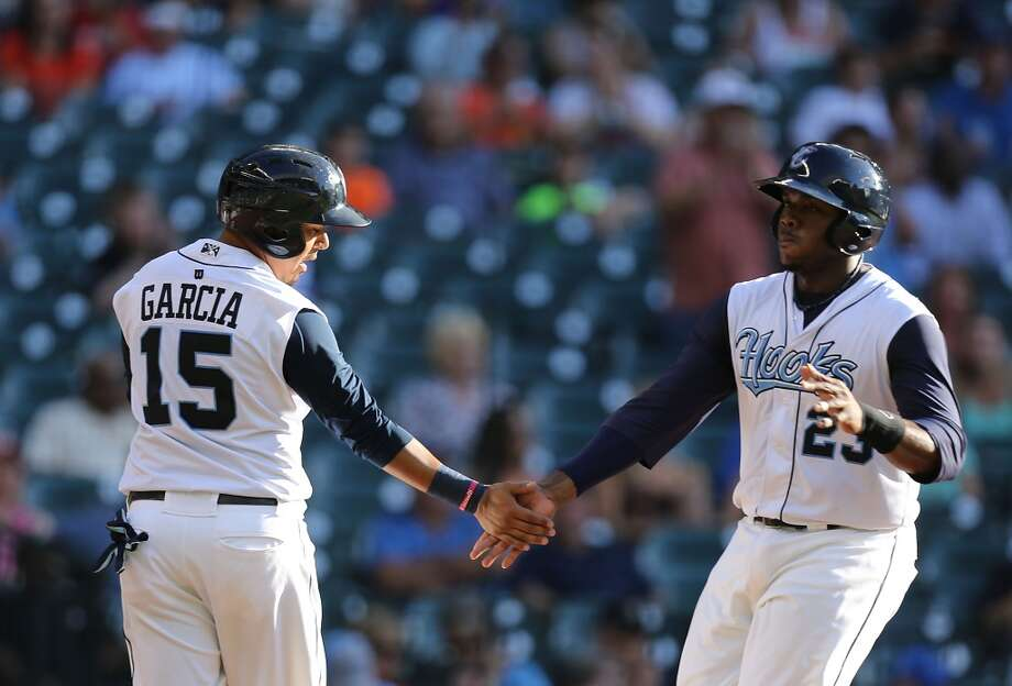 Corpus Christi Hooks Telvin Nash right, slaps hands with teammate Rene Garcia after scoring a run against San Antonio Missions during the second inning of Minor League Baseball game action at Minute Maid Park Tuesday, June 10, 2014, in Houston. ( James Nielsen / Houston Chronicle ) Photo: James Nielsen, Houston Chronicle