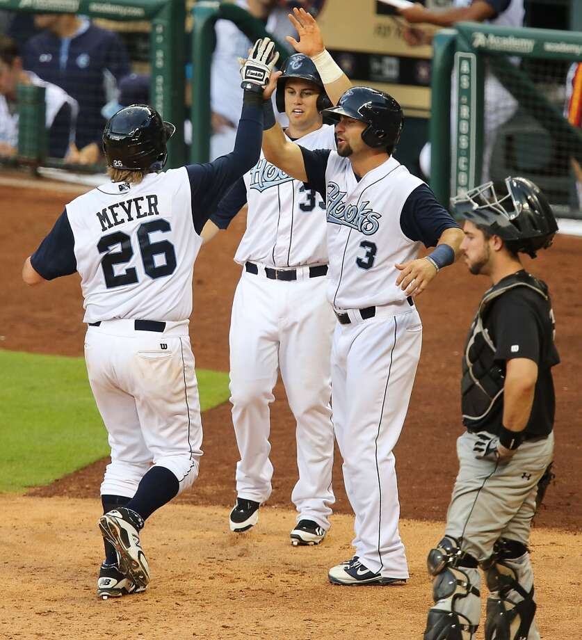 Corpus Christi Hooks Jonathan Meyer left, celebrates at home plate with teammates Preston Tucker 2nd from left, and Andrew Aplin 2nd from right, after hitting a home run as San Antonio Missions catcher Austin Hedges right, looks on during the fifth inning of Minor League Baseball game action at Minute Maid Park Tuesday, June 10, 2014, in Houston. ( James Nielsen / Houston Chronicle ) Photo: James Nielsen, Houston Chronicle