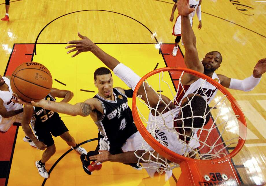 San Antonio Spurs guard Danny Green (4) drives to the basket over Miami Heat center Chris Bosh (1) and  guard Dwyane Wade (3)during the first half in Game 3 of the NBA basketball finals, Tuesday, June 10, 2014, in Miami. (AP Photo/Wilfredo Lee) ORG XMIT: AAA129 Photo: Wilfredo Lee / AP
