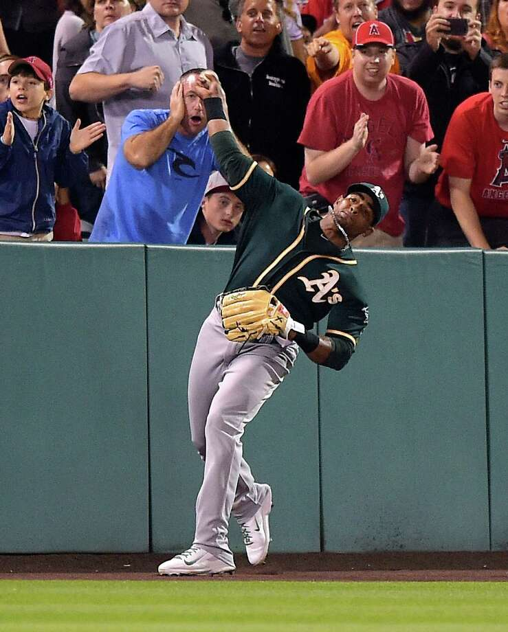 "A's left fielder Yoenis Céspedes booted the ball into the corner, retrieved it and threw a 300-foot strike to the catcher. ""It's the most improbable thing I've ever seen on a baseball field,"" says Oakland closer Sean Doolittle. Photo: Mark J. Terrill / Associated Press / AP"