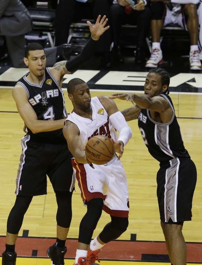 Heat guard Dwyane Wade (3) looks to pass under pressure from Spurs guard Danny Green (4) and forward Kawhi Leonard (2). Photo: Lynne Sladky, Associated Press