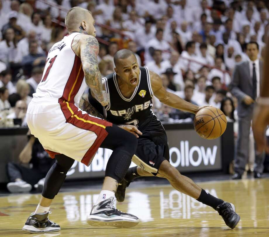 Spurs guard Patty Mills (8) drives around Heat forward Chris Andersen (11). Photo: Wilfredo Lee, Associated Press